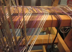 The yarn travels from the reed to the heddles