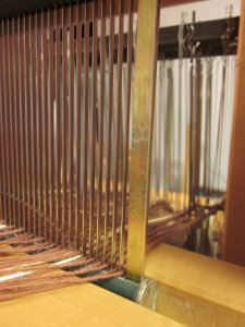 Watching the brown yarn go through the reed & the heddles!